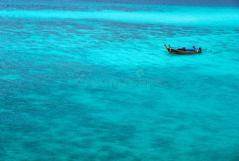 The sea looks out to emerald blue. There is 1 floating boat quietly on the waves in the Andaman Sea royalty free stock photography