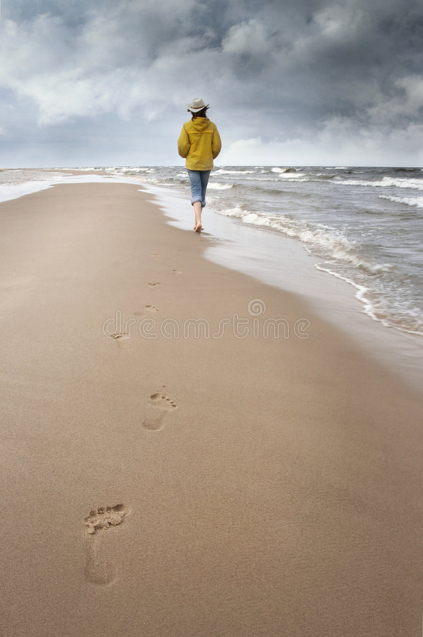 Sea and lowering clouds. Woman walks along coast and see on storm clouds stock images