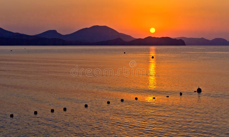 The sea and the mountains in the rays of the rising sun royalty free stock image