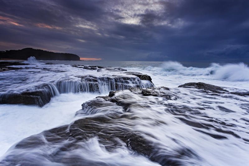 Sea Narrabeen 05 rocks. Strong tide wave undermining sandstone rocks near Collaroy northern beaches of Sydney at sunrise. Dramatic weather hides rising sun royalty free stock image