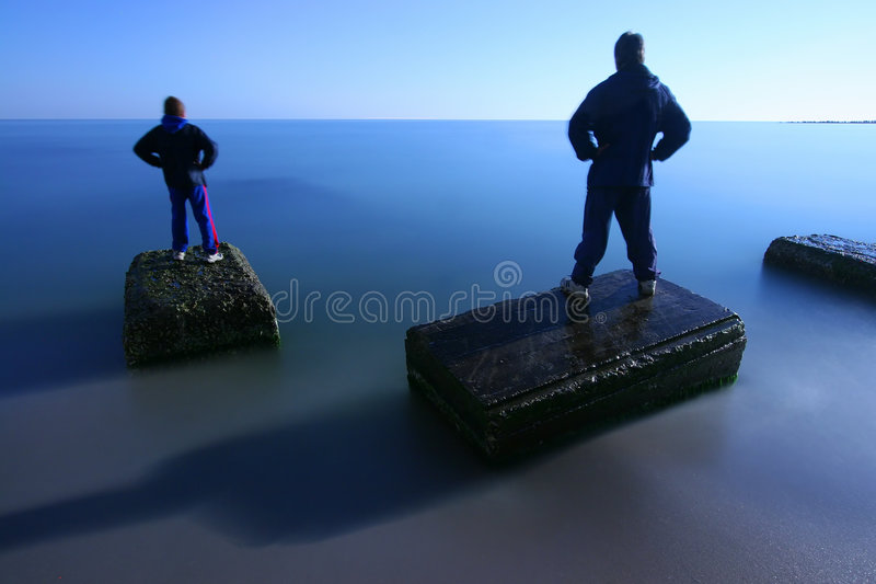 On sea in night. Two people on sea in night royalty free stock images