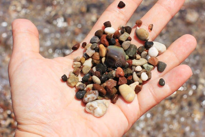 Sea pebble stones in open hand royalty free stock photos