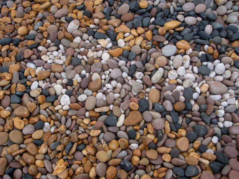 Sea pebbles on beach, various colors and types of stone. Multicoloured stones - black, white, yellow. Sea pebbles on beach, various colors and types of stone stock photography
