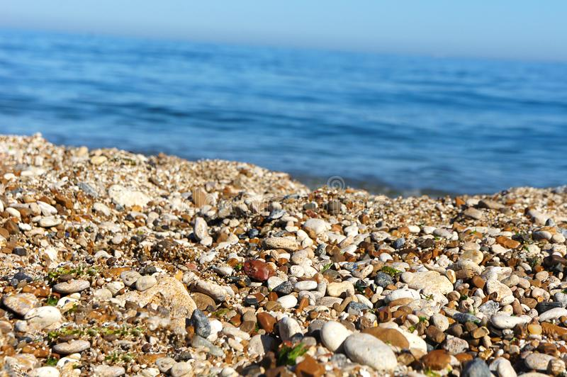Sea pebbles sand on the background of the sea. Background, bright pebbles blue sea behind royalty free stock images
