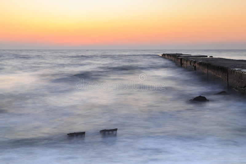 Sea and pier at dawn, calm royalty free stock image