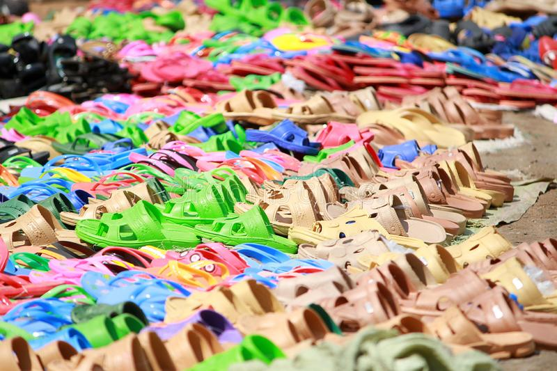 A sea of plastic sandals at a market in Accra, Ghana. Vivid colors displayed along the streets Accra in pink, blue, brown, and green stock photos