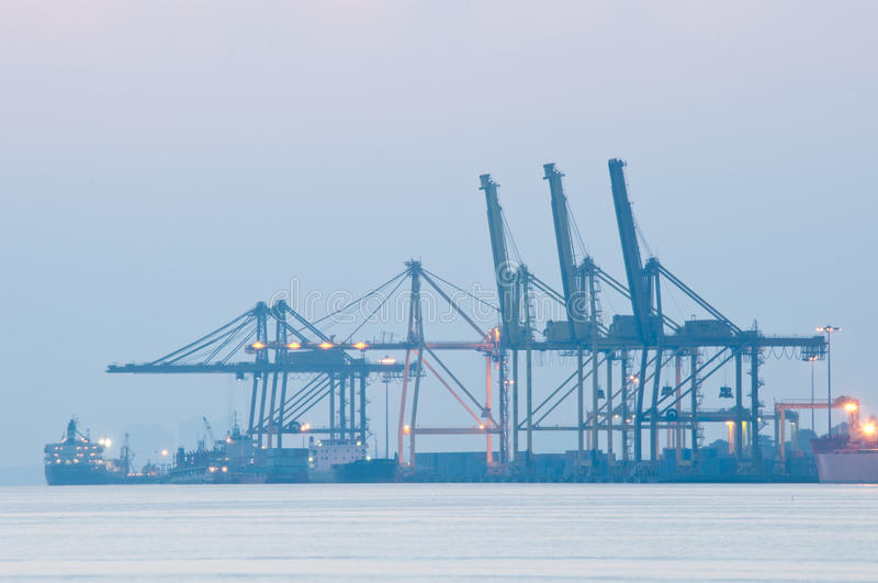 Sea Port. Row of crane at a sea port for loading and unloading of cargo during a misty hour royalty free stock image