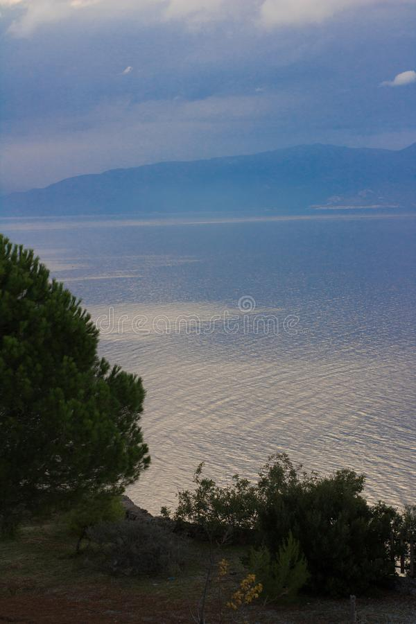 sea reflection trees view from a balcony in greece stock photo
