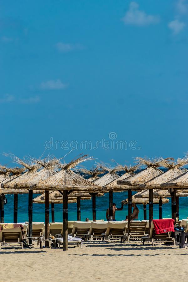 Sandy beach, sun loungers and thatched sun umbrellas royalty free stock images