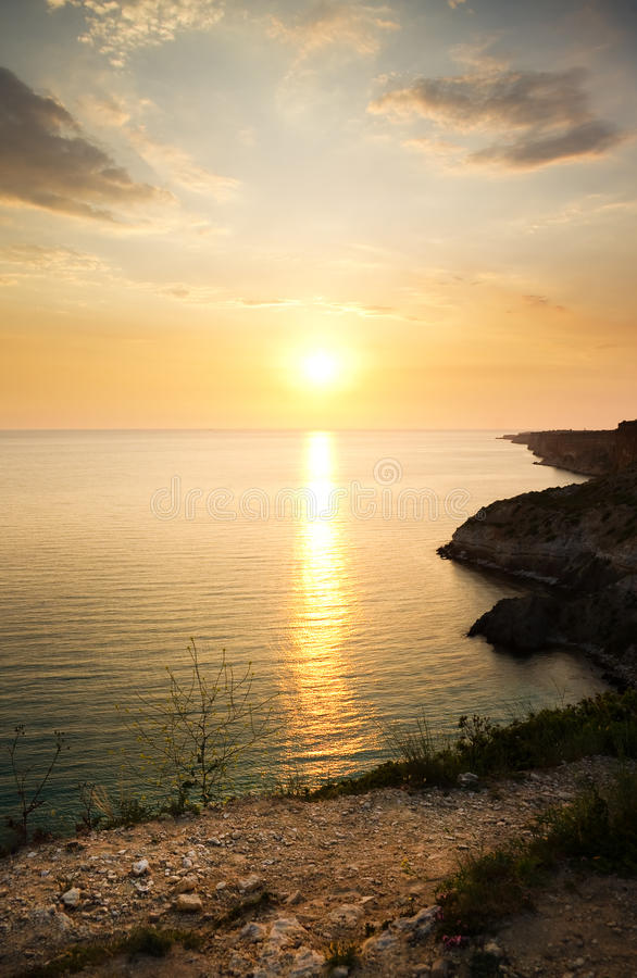 Sea and rock at the sunset. stock photo