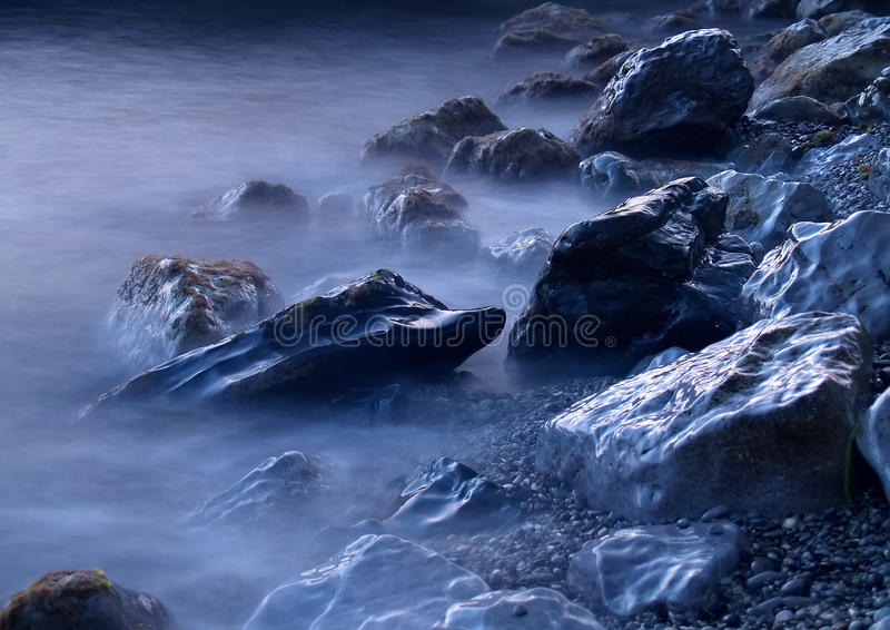 Sea rocks in fog stock images
