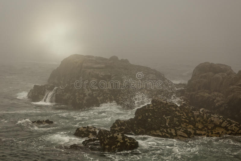 Sea rocks in a foggy sunset royalty free stock photos