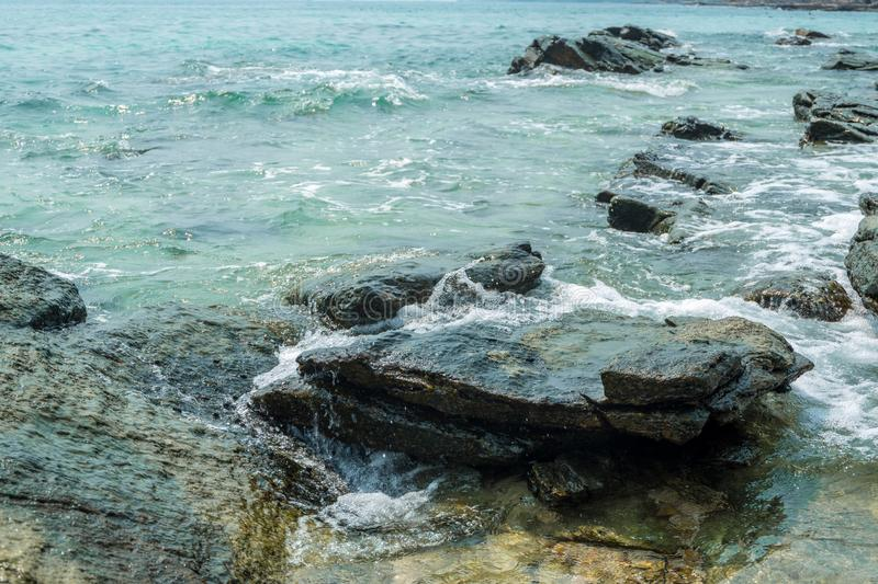 Sea rocks are surrounded by mini splashing wave stock image