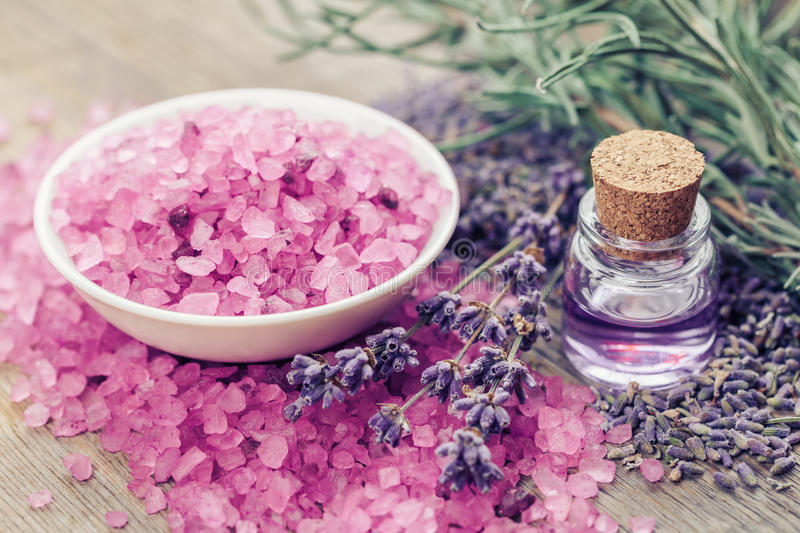Sea salt, bottle of essential oil and lavender flowers. Aromatic sea salt, bottle of essential oil and lavender flowers. Selective focus royalty free stock images