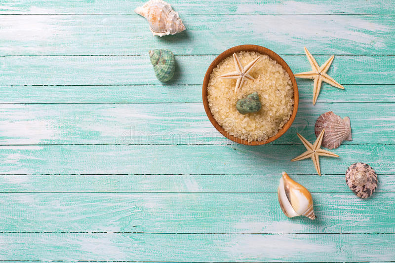 Sea salt in bowl with sea objects on turquoise wooden backgroun royalty free stock images
