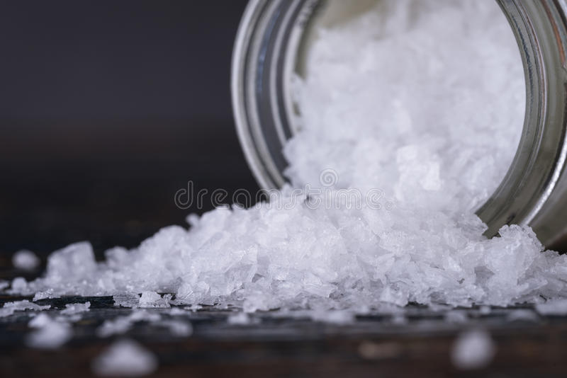 Sea Salt Flakes Spilled from a Spice Jar royalty free stock images