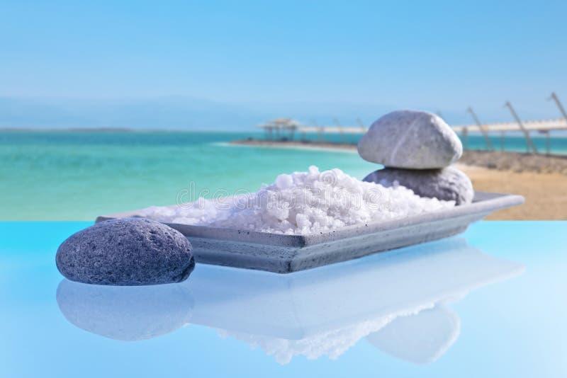 Sea salt on a glass table with stones and cockleshells stock photography