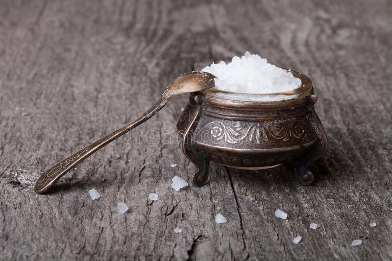 Sea salt in an old utensils and a small spoon on a wooden table royalty free stock photos