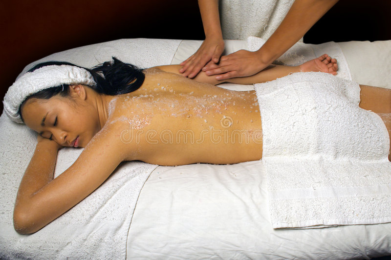 Sea Salt Scrub Massage Rub. Sea Salt Scrub Massage treatment being given to a young Asian woman by an African American woaman who has a motion blur effect on the stock images