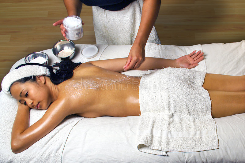 Sea Salt Scrub Massage Treatment in a spa setting. Sea Salt Scrub Massage treatment being given to a young Asian woman by an African American woaman who has a royalty free stock photo