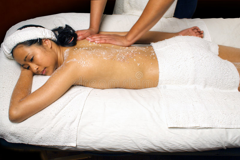 Sea Salt Scrub Massage Treatment in a spa setting. Sea Salt Scrub Massage treatment being given to a young Asian woman by an African American woaman who has a royalty free stock photos