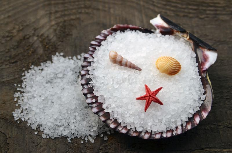 Sea salt in a seashell on old wooden background.Healthy eating,spa or beauty treatment concept. Selective focus royalty free stock images