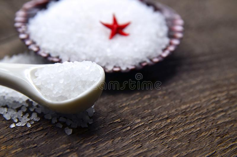 Sea salt in a white spoon on old wooden background.Healthy eating,spa or beauty treatment concept. Soft focus royalty free stock photography