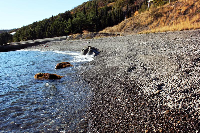 Sea, sand and forest. Black Sea in autumn, beach and stones royalty free stock photos