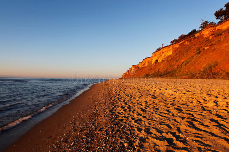 Sea with a sandy beach and sky in the rays of the rising sun.  royalty free stock image