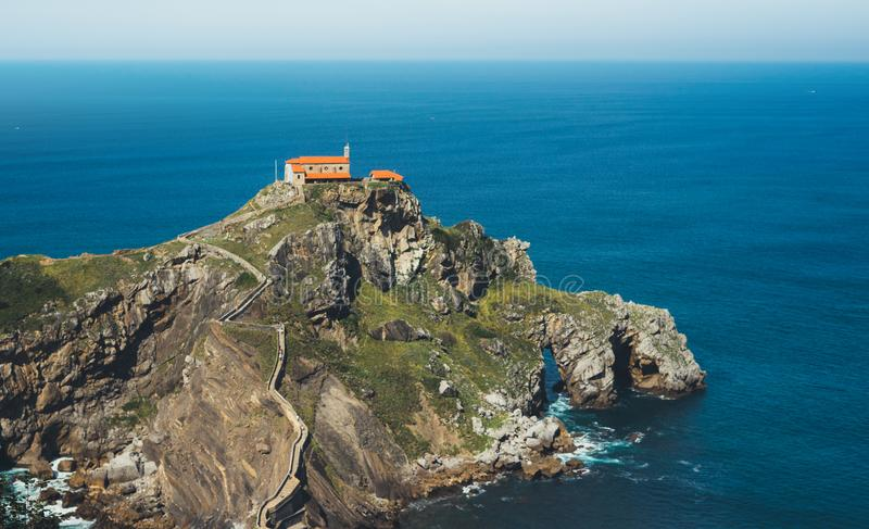 Sea scape on background gaztelugatxe steps sun huan, hipster girl looking on nature horizon ocean, relax holiday, blank space blue royalty free stock photography