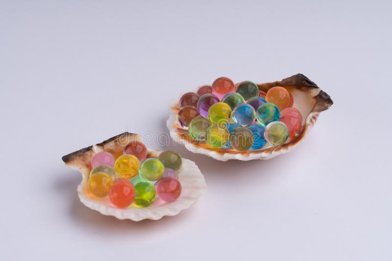 Sea shell with multicolored hydrogel balls macro stock image