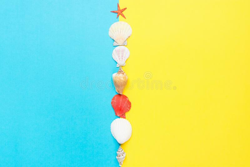 Sea Shells of Different Shapes Spiral Flat Red Starfish on Split Duo Tone Yellow Blue Background. Summer Sale Vacation Beach Party royalty free stock photo