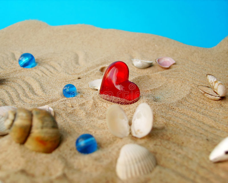 Sea shells and heart. Sea shells, sand and red heart stock photography