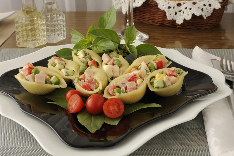 Sea shells pasta stuffed with vegetables and ham. Large pasta shells stuffed with vegetables and ham royalty free stock photo