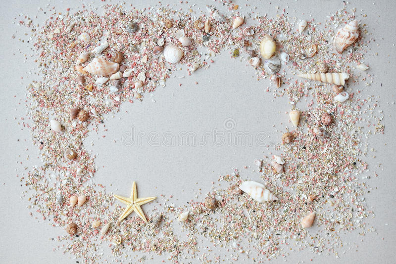 Sea shells and pink sand with a starfish on a paper background with empty space for text.  stock images