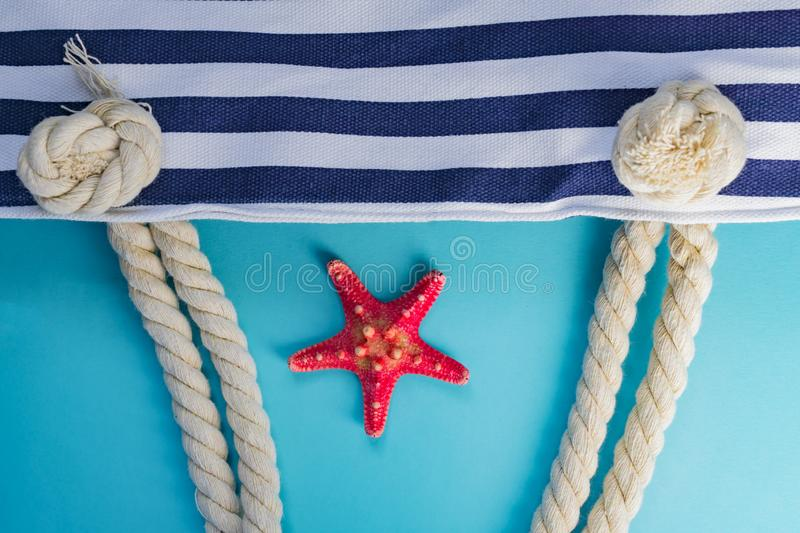 Sea shells, starfish and textile stiped navy bag with rope knots on light blue background. summer holiday and vacation concept stock photos