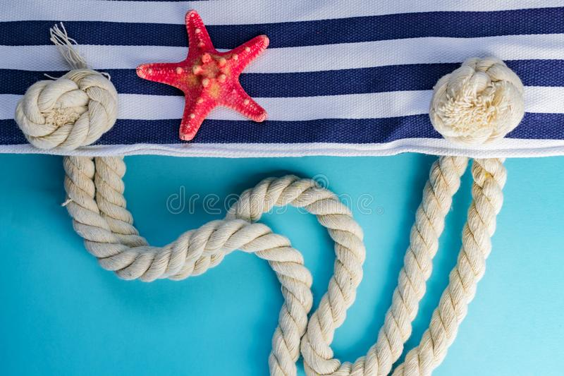 Sea shells, starfish and textile stiped navy bag with rope knots on light blue background. summer holiday and vacation concept.  royalty free stock photo