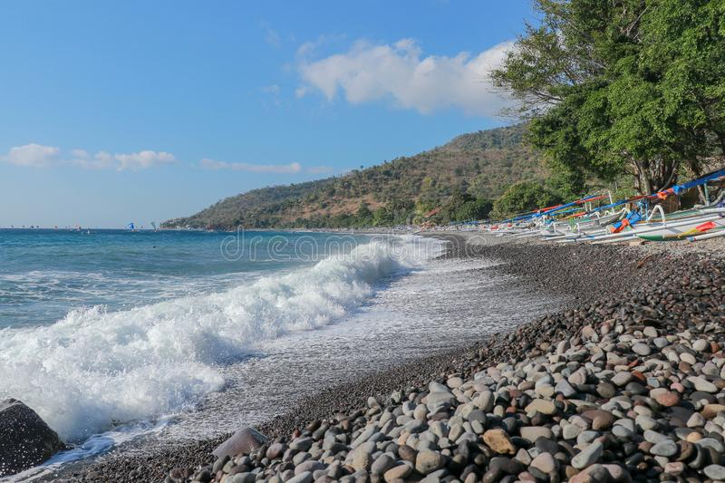 Sea shore break attacks a stony beach in Bali, Indonesia. Sea foam rolls over a pebble beach. The ocean shows off its power in ful. L beauty. Tropical scenery royalty free stock photography