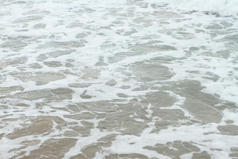 Sea shore foamy water. Detail royalty free stock photo