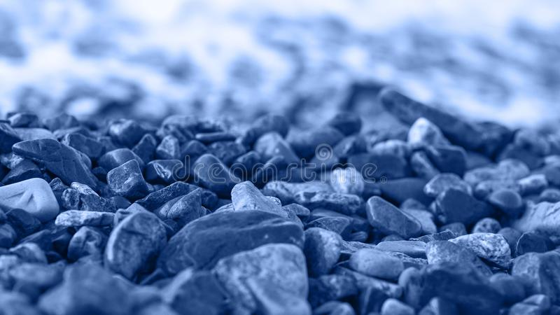 Sea shore stones, surf, selective focus. Nature theme, toned in blue.  stock image