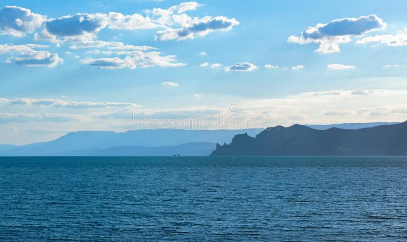 The sea with the silhouette of a jagged rocky shore in the distance with mountains stock photo