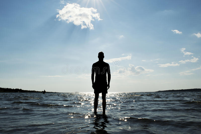 Sea silhouette of a man. Silhouette of man in front of glittering sea royalty free stock photos