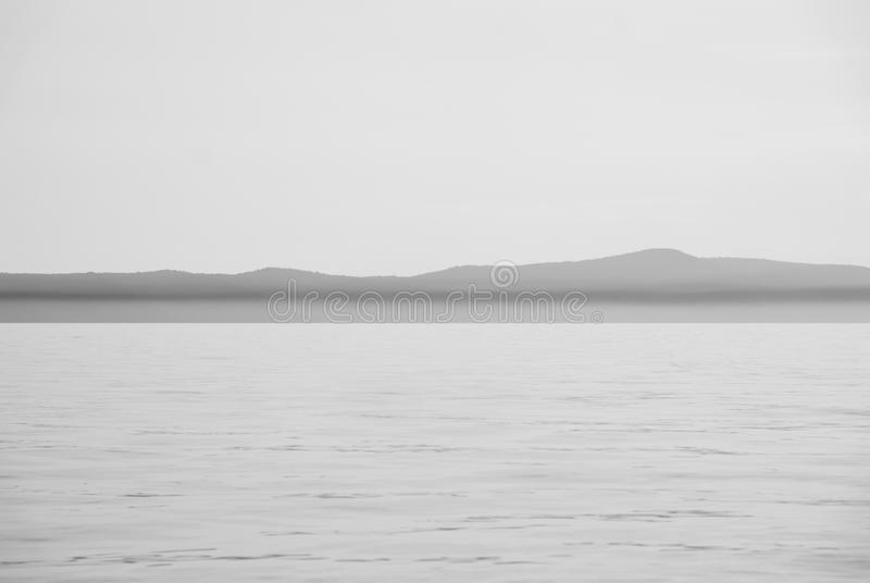 Sea and sky with land horizon royalty free stock photography