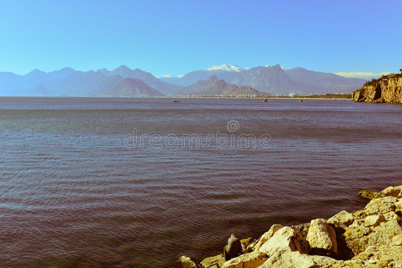 Sea with sky and mountains. Sea near the mountain, sky with clouds and buildings stock photos