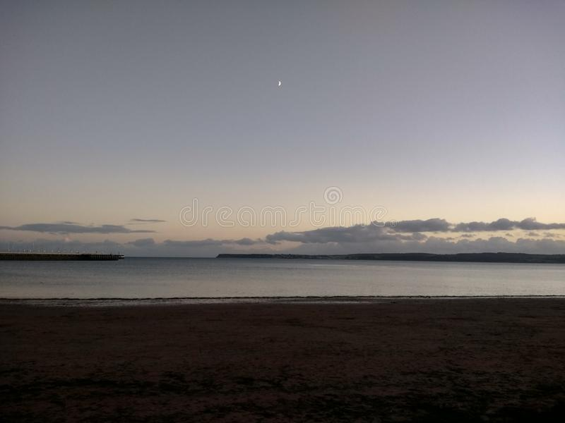 Sea with small moon peeping through the cloud. stock photo