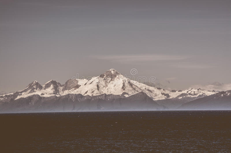 Sea and snowcapped mountains royalty free stock photography