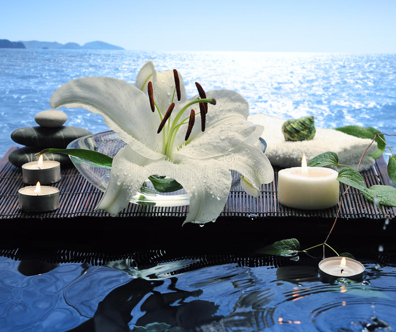 Sea spa. With white lily and floating burn candles stock photo