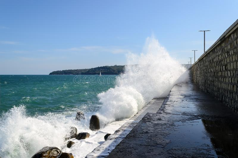Sea splashing waves crash on a breakwater. Walking path along the groyne is flooded with sea water during a small storm on a sunny royalty free stock image