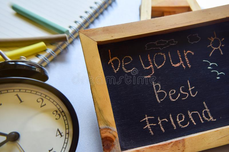 Sea su manuscrito colorido de la frase del mejor amigo en la pizarra, el despertador con la motivación y conceptos de la educació fotografía de archivo libre de regalías