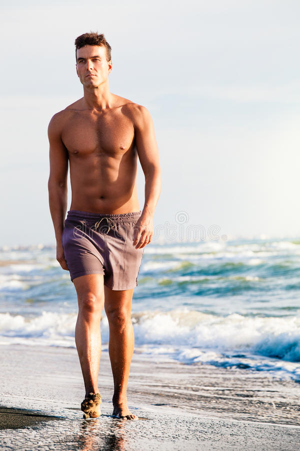 Sea in summer. Man walking on the shore. A nice Italian man in shorts walking along the seashore. Waves and blue sea behind him. Lean physique and rightly royalty free stock image